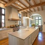 Large Tuscan galley kitchen with white cabinets, paneled appliances, medium tone hardwood floors, an island, recessed panel cabinets and white backsplash