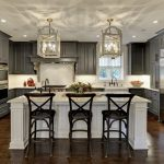 Large elegant u shaped eat in kitchen with gray cabinets, white backsplash, stainless steel appliances, dark hardwood floors, an island, raised panel cabinets and a farmhouse sink