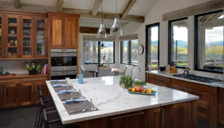 Large rustic u shaped eat in kitchen with a farmhouse sink, shaker cabinets, medium tone wood cabinets, stainless steel appliances, an island, marble countertops, white backsplash, stone slab backsplash