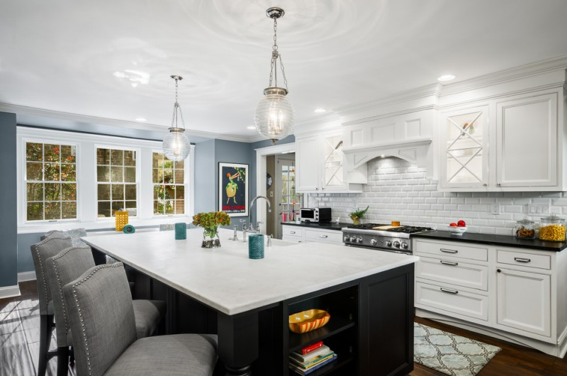 Large traditional l shaped kitchen with a farmhouse sink, recessed panel cabinets, white cabinets, marble countertops, white backsplash, subway tile backsplash, stainless steel appliances, dark hardwood