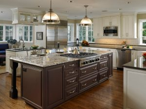Large traditional u shaped eat in kitchen with a farmhouse sink, raised panel cabinets, beige cabinets, white backsplash, subway tile backsplash, stainless steel appliances, dark hardwood floors