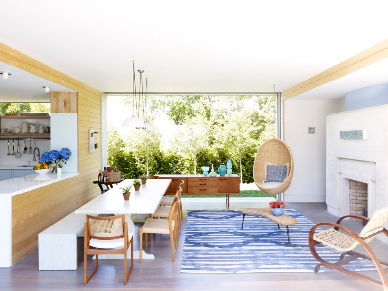 Mid sized kitchen with a standard fireplace white painted kitchen table benches and chairs accented blue and white rug rattan coffee table and chairs