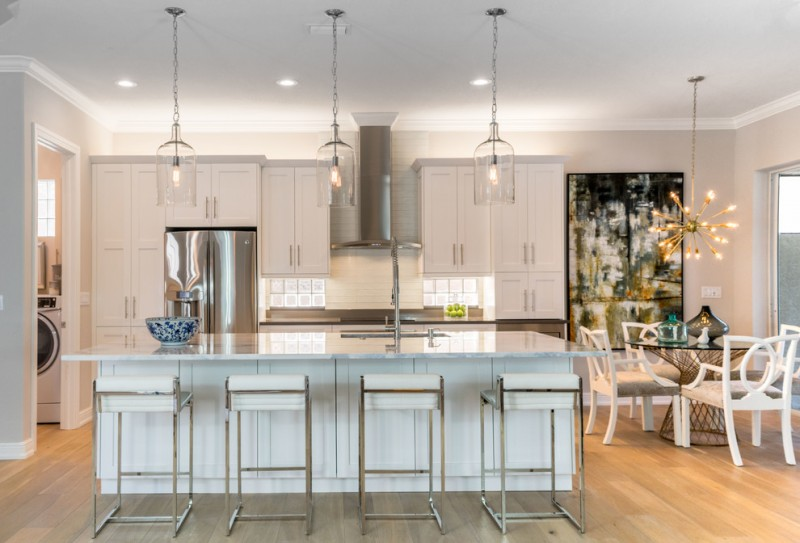 Mid sized transitional galley open concept kitchen with shaker cabinets, white cabinets, marble countertops, white backsplash, glass tile backsplash, stainless steel appliances, light hardwood floors, an