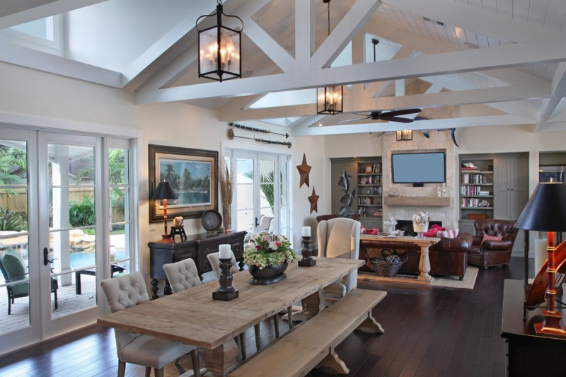 Mountain style dining room with beige walls, dark hardwood floors, a standard fireplace, a stone fireplace surround and brown floors