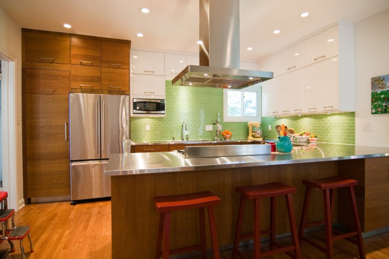Silver surface appliances red painted wooden bar stools wooden island with silver countertop light toned wooden floors wooden cabinets white cabinets