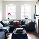 Small eclectic enclosed living room idea white walls, medium tone hardwood floors and a standard fireplace large sectional sofa ottoman coffee table
