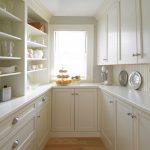 U Shape White Kitchen Idea With White Lower & Upper Cabinets White Countertop Centered Glass Window Textured White Backsplash Built In White Shelves