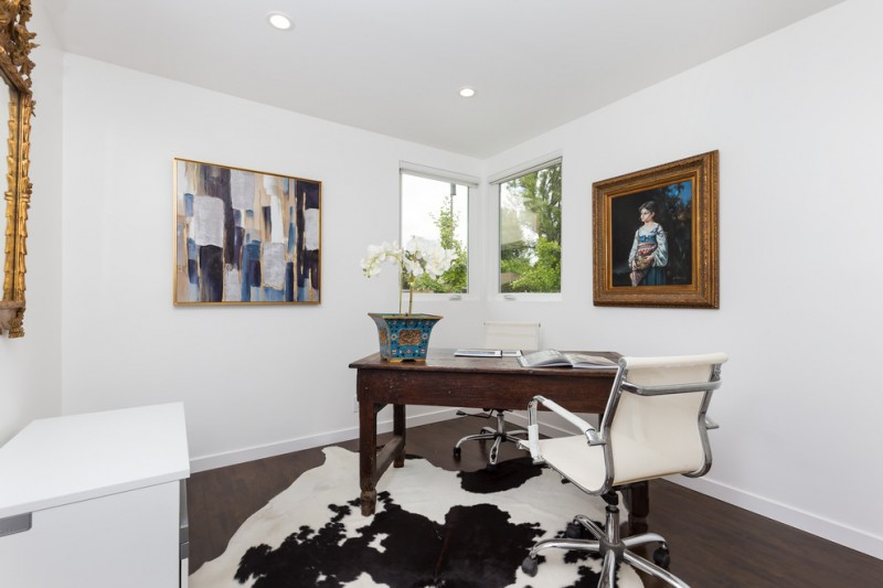 airy and simple white home office with corner glass windows wall arts dark toned wood working table modern working chair in white cowhide area rug dark toned wood floors white walls