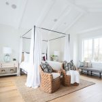 Antique Black Wrought Iron Bed Frame White Bedding A Couple Of Wicker Chairs Soft Textured Woven Rug Medium Toned Wood Floors White Bedside Tables Black White Bench Under Window