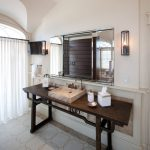 antique table for bathroom vanity with brown stone sink and large mirror