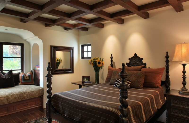antique wood bed frame antique bedside tables mirror with dark toned wood frame beige walls ceilings with exposed beams