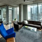 apartment living room ideas cirrus hugger ceiling fan clear glass cocktail table futuristic blue armchair dark grey rug brown sofa and armchairs floor lamp