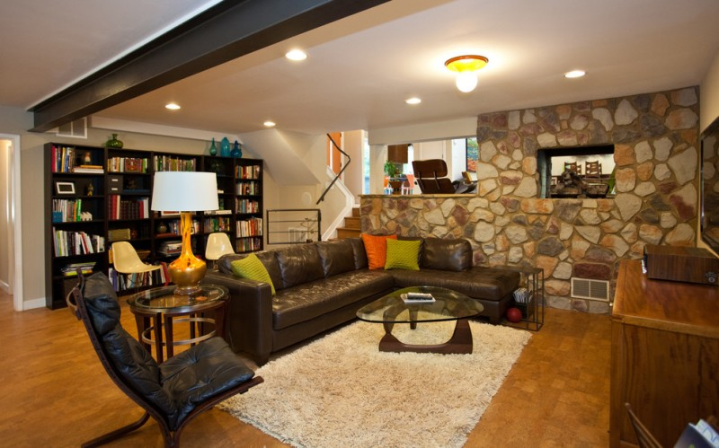 basement living room idea stone finished walls hardwood floors dark colored leather couch glass top center table round glass top side table white area rug white ceilings