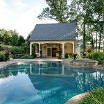 beautiful pool with beautiful pool house with high blue roof,  cream wall, cream wooden siding wall, rattan chair set, plants