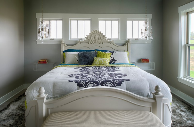 bed frame with artistic craft headboard in white white comforter with dark classic motifsjs light grey walls with upper glass windows at back of bed fluffy grey bedroom rug white settee