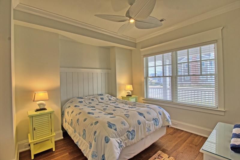 bed frame with wall mounted headboard in white a pair of yellow bedside tables a couple of table lamps dark toned wood floors ceiling fan with center light fixture