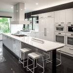 black and white kitchen black stone kitchen flooring double ovens recessed lighting white bar stools built in refrigerator white island hood