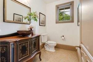 black vanities with golden carving, wooden countertop, vessel sink, mirror, limestone floor, toilet