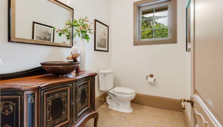 black vanities with golden carving, wooden countertop, vessel sink, mirror, limestone floor, toilet