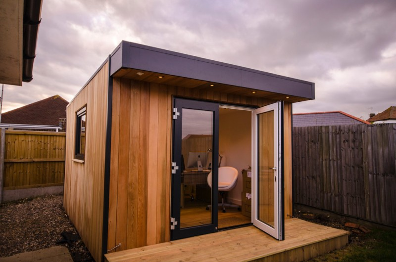 boxy private office built from woodboards with black lines details glass door with black wood frames