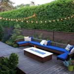 Built In Seating With Blue Foam Base And Multicolored Accent Pillows Firepit Woodboard Base Strings Of Little Ball Lamps Woodboard Rail System