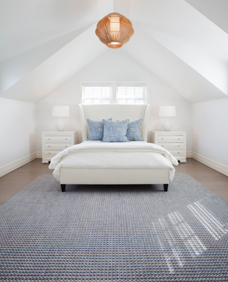 clean white bed frame with higher and wider headboard a couple of bedside tables in white accent blue pillows textured blue area rug white walls white pointed ceilings