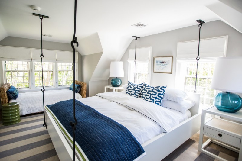 coastal bedroom idea hanging bed frame in white white & navy blue bedding idea clean white bedside tables rattan made settee with white comforter white blue stripes area rug