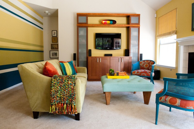 colorful living room in modern style turquoise center table with wood legs blue chairs with sun flower motifs yellow couch with colorful accent pillows white finished concrete floors