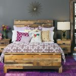 Contemporary Bedroom Design Bold Patterned & Multicolored Bedding Eclectic Wood Bedroom Furniture Bold Purple Bedroom Rug Wood Bedside Tables Hand Shaped Wooden Chair Wooden Vertical Shelving Unit