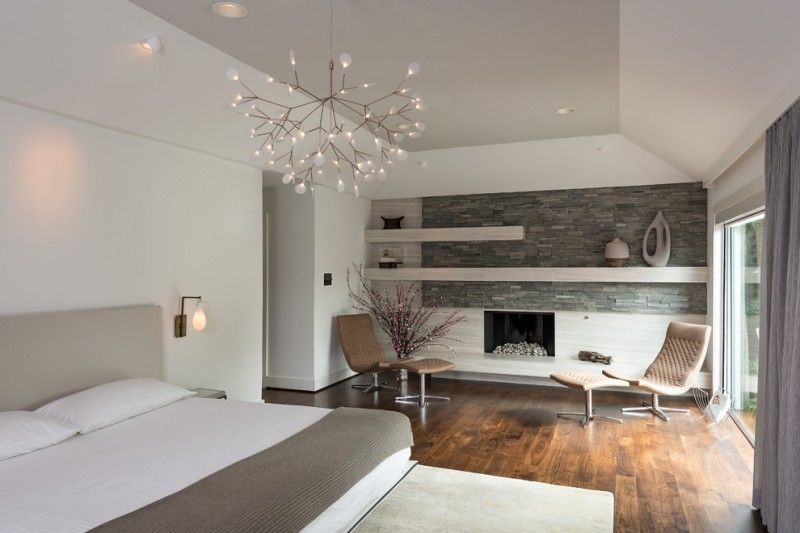 contemporary bedroom idea bed frame with beige headboard white bedding with grey blanket dark toned wood floors standard fireplace feature with stone surround modern chairs unique pendant lamp
