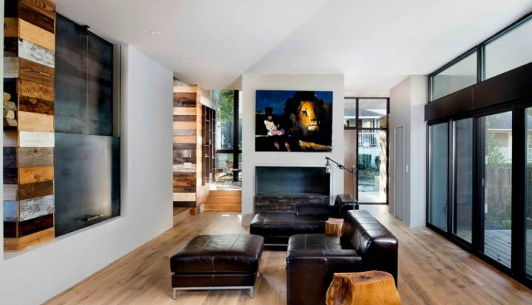 contemporary family room with dark leather sectionals wood side tables light toned wood floors hidden media cabinet with shutter white walls
