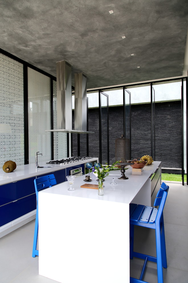 contemporary kitchen idea concrete ceilings with recessed lighting fixtures solid white countertop glossy blue flat panel cabinets solid white breakfast nook with blue chairs