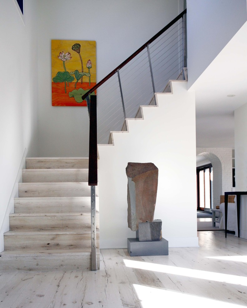 contemporary staircase with light toned wood steps and stylish cable railings whitewashed wood floors