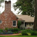 cottage house with chimney and exposed brick wall and brick pathways multicolored shrubbery white painted deck wooden walls white framed glass windows white fences