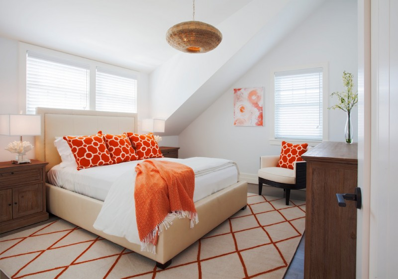 cream bed frame with higher headboard white bedding with bright orange shams & blanket cream area rug with bright orange decorative lines a cream chair with orange accent pillow wooden bedside