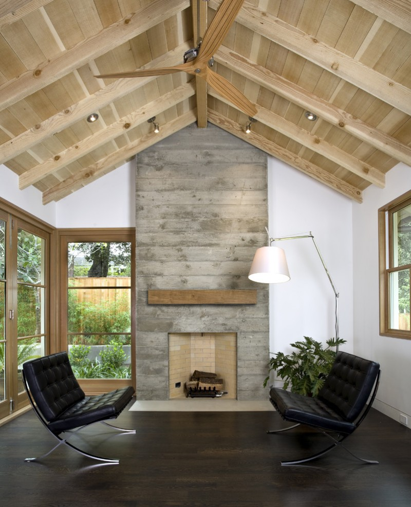 custom agrarian concept living room with industrial leather chairs in black board look like fireplace made of concrete dark hardwood floors white walls arched ceiling made of Oak