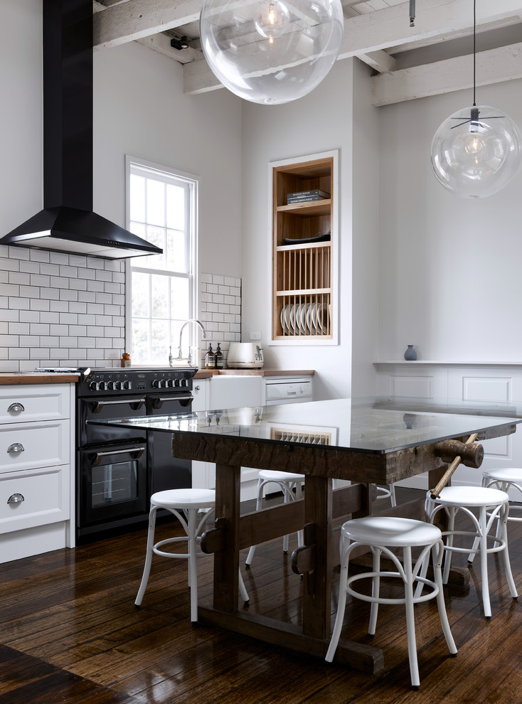 dark & light industrial kitchen recessed shelving unit made of wood white subway tiles backsplash white walls glass top dining table white bar stools white cabinets dark toned wood floors