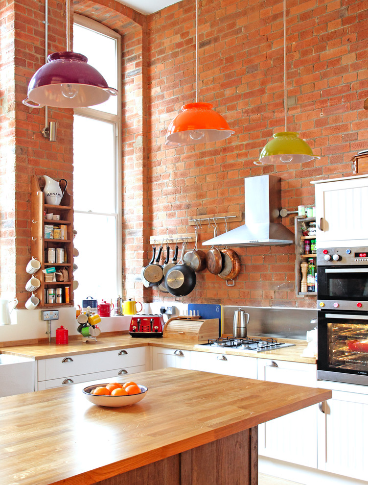 eclectic kitchen idea with a narrow floating industrial shelving butcher block worktop light finished kitchen appliances red bricks walls pop colored pendant lamps