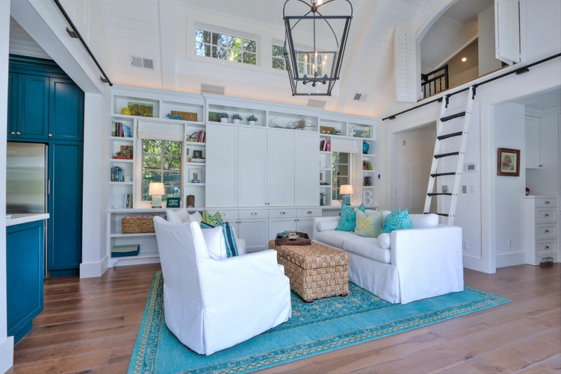 enclosed living room with coastal theme white sofa slipcover textured wood coffee table blue area rug medium toned wood floors recessed sheves in white white ladder