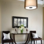 Entrance Hall With Entrance Console In Dark Finishing Side Chairs In Dark Finishing Light Grey Accent Pillows Large Hanging Light Fixture