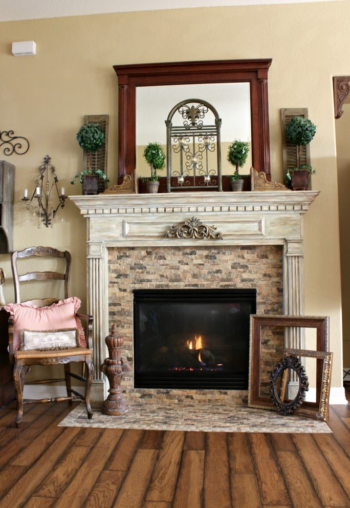 french country fireplace idea old look wood chair with accent pillow wood floors beige walls with many wall decorations