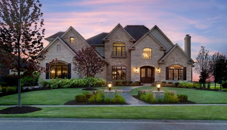 front yard landscape with curved pathway and lighted pillars in flowers bed double front door with glass and wrought iron exposed brick walls