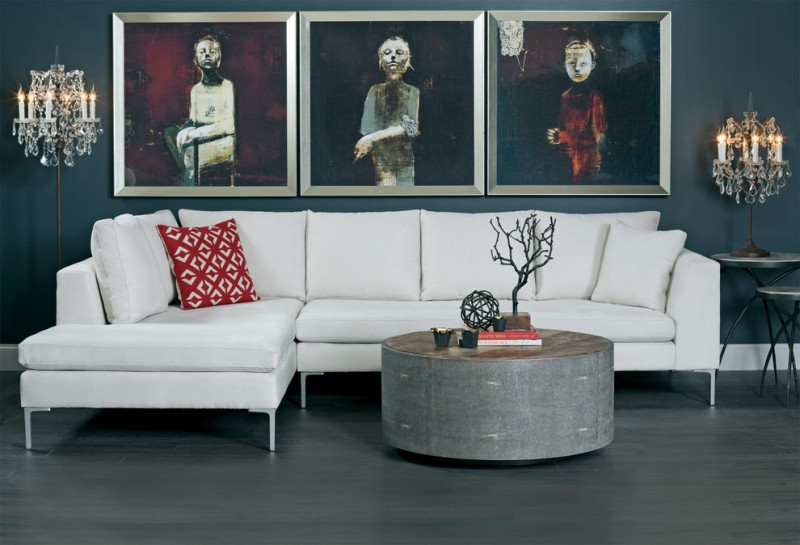 gothic themed living room white sectional with accent pillow rounded coffee table with small ornaments on top solid black floors three artistic paintings on wall a pair of chandelier table lamps