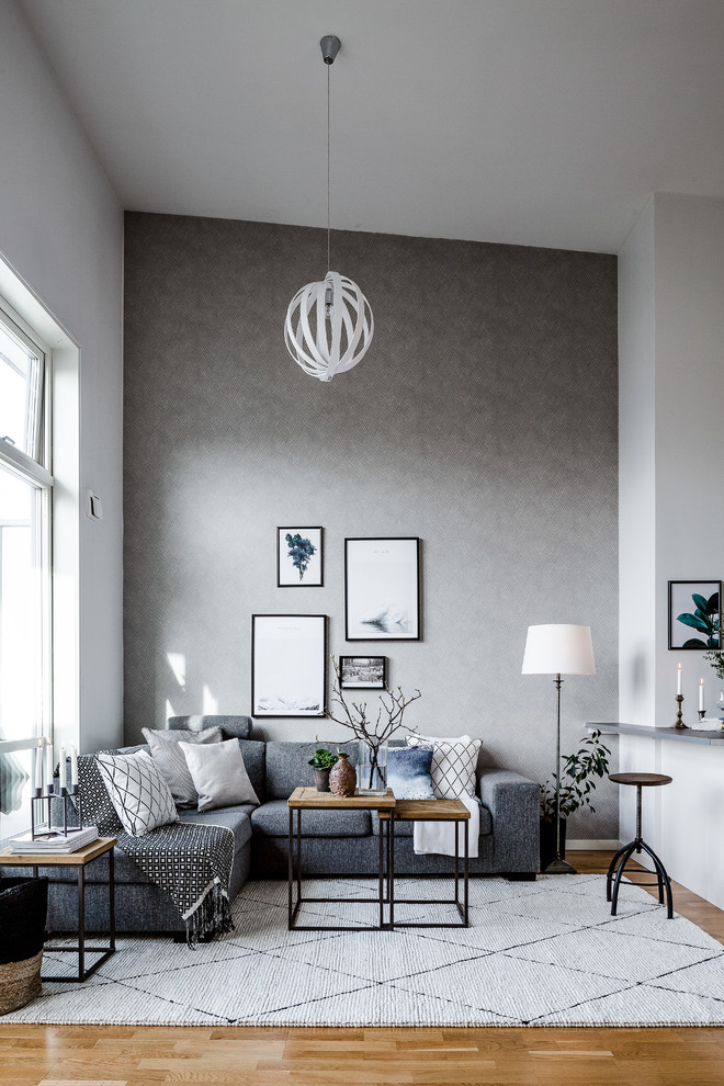 grey accent walls with decorative frame ornaments L shaped sectional in grey white accent pillows white area rug with black decorative lines industrial coffee table industrial side table s