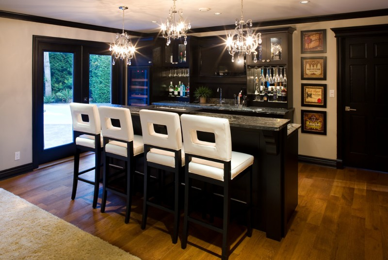 home bar setup royal cut crystal maria theresa chandelier golden teak crystal upper and lower bar counter white cushioned barstools black cabinet light hardwood floor granite countertop