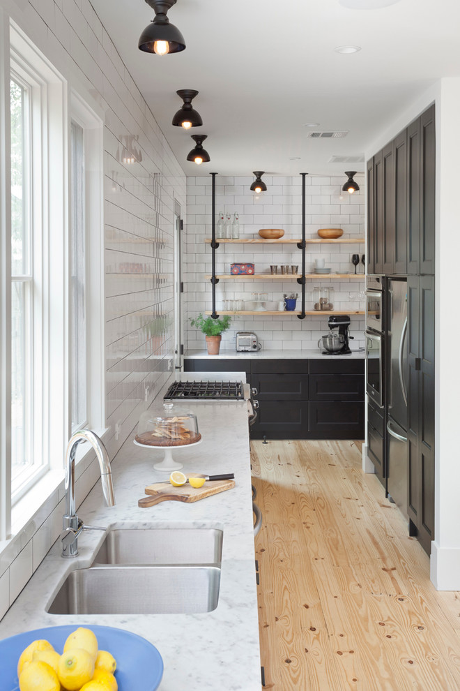 industrial open shelves supported by plumbing pipes white countertop double bowl sinks white subway tiles backsplash light toned wood floors flat panel cabinets in black