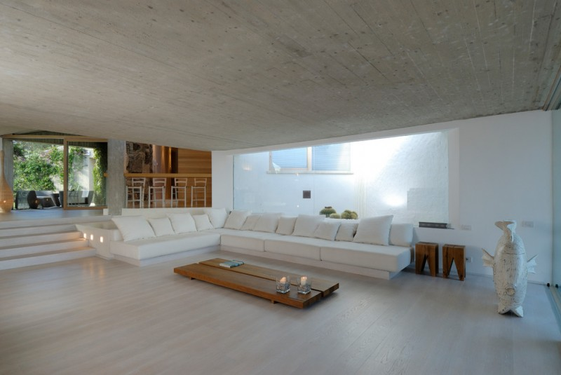 large sized contemporary living room white sectionals with white accent pillows lower & flat hardwood coffee table white walls light floors concrete ceilings