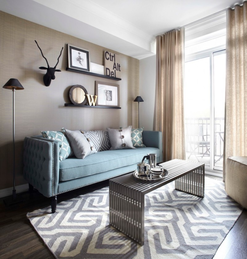 light blue sofa with accent pillows modern patterned area rug in blue and white chrome center table gold toned draperies beige walls with simply decorative frames