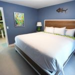 Lightweight Wood Bed Frame With Headboard Blue Walls White Ceilings Grey Vinyl Floors Blue Bedside Tables Green Table Lamps With White Shading