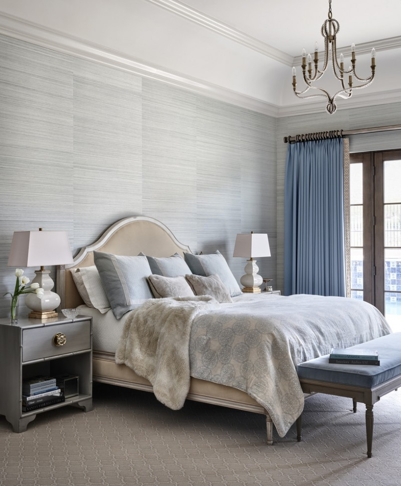 luxurious bed frame with headboard grey walls white ceilings blue drapery settee with blue comforter grey bedroom rug with thin white patterns classic chandelier grey finishing bedside tables